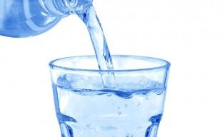 تصویری از یک بطری آب معدنی در حال پرکردن یک لیوان