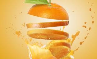 تصویری هنری از یک لیوان آب پرتقال طبیعی با برشهای پرتقال